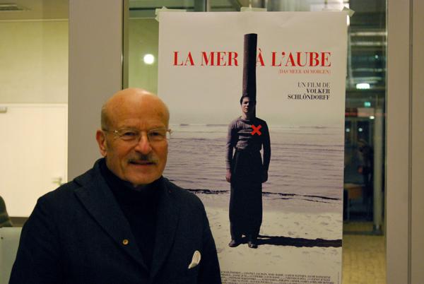 Schlöndorff vor französischem Plakat. Quelle: https://de.ambafrance.org/IMG/jpg/2012-01-31_Schlondorf_12__web.jpg?5316/8f94c4425e41d288705b370bdd54d3d797a6ba1f